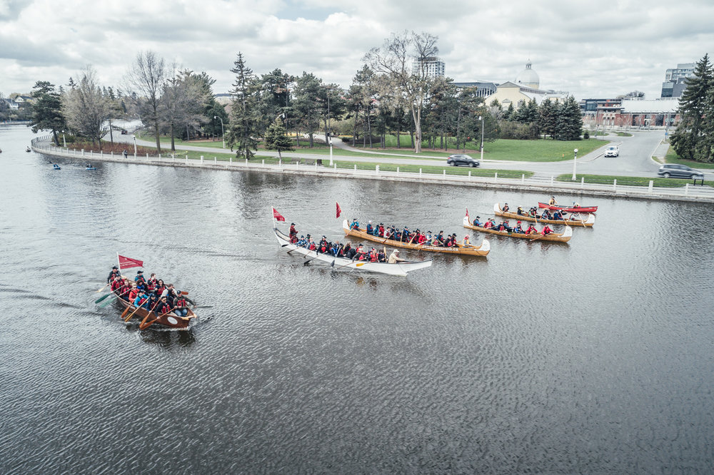 5 voyageur canoes on the river, photo is an overhead shot