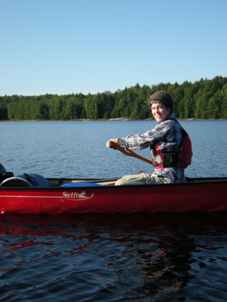 Smiling Person Paddling Canoe