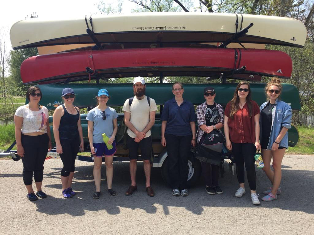 Adult paddling group in front of canoe rack