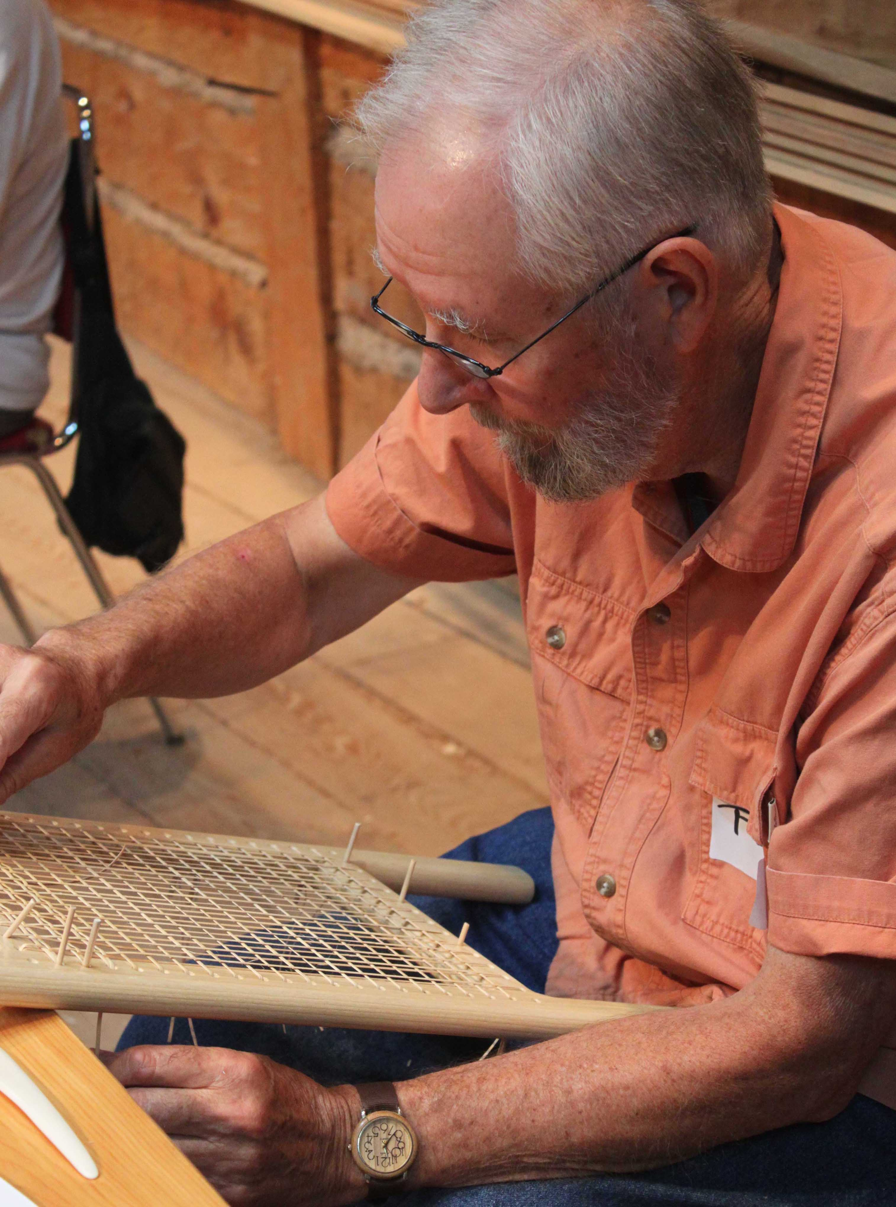 Man caning a canoe seat