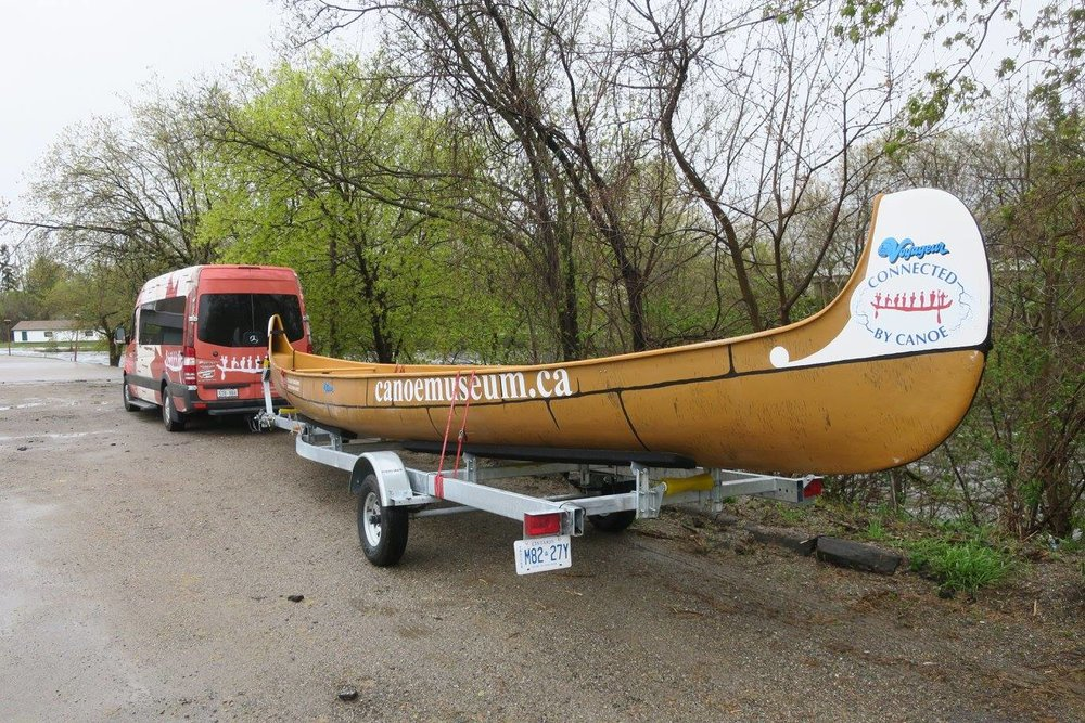 the canoe used in the connected by canoe journey, on it's trailer being towed behind the museum van
