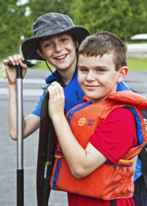 Two boys smiling with lifejackets and paddles